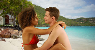 Romantic couple sitting on beach staring into each other`s eyes. Royalty Free Stock Image