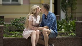 Romantic couple sitting on bench, girl kissing her boyfriend on cheek, feelings. Stock footage stock video