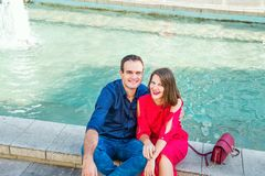 Romantic couple sitting on the bench near the city fountain and enjoying moments of happiness. Love, dating, romance. Lifestyle an. D tourism concepts. Selective Royalty Free Stock Photos