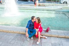 Romantic couple sitting on the bench near the city fountain and enjoying moments of happiness. Love, dating, romance. Lifestyle an. D tourism concepts. Selective Stock Images