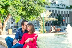 Romantic couple sitting on the bench near the city fountain and enjoying moments of happiness. Love, dating, romance. Lifestyle an. D tourism concepts. Selective Royalty Free Stock Image
