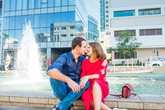 Romantic couple sitting on the bench near the city fountain and enjoying moments of happiness. Love, dating, romance. Lifestyle an. D tourism concepts. Selective Stock Photo