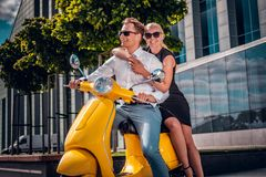 Romantic couple sitting on a classic Italian scooter on the street of a modern part of a European city stock photo