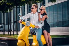 Romantic couple sitting on a classic Italian scooter on the street of a modern part of a European city stock photography