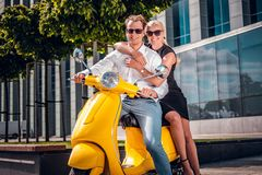 Romantic couple sitting on a classic Italian scooter on the street of a modern part of a European city royalty free stock images
