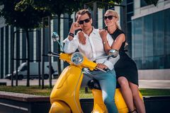 Romantic couple sitting on a classic Italian scooter on the street of a modern part of a European city royalty free stock photography
