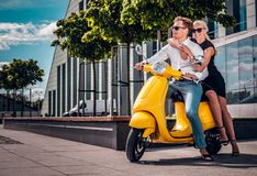 Romantic couple sitting on a classic Italian scooter on the street of a modern part of a European city royalty free stock photos