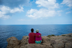 Romantic couple sitting on a cliff and admirig wonderful seascape stock photo