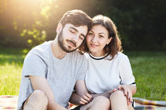 Romantic couple sitting close to each other while resting outdoor at nature during summer day, feeling happiness and relaxation. P Stock Photos