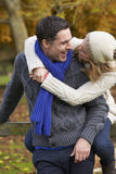 Romantic Couple Sitting On Fence In Autumn Woodland Stock Image