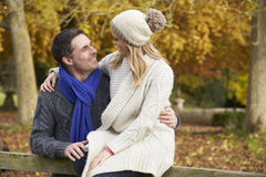 Romantic Couple Sitting On Fence In Autumn Woodland Royalty Free Stock Photos