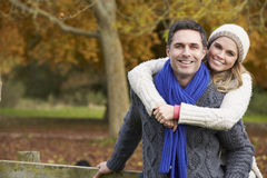 Romantic Couple Sitting On Fence In Autumn Woodland Royalty Free Stock Photography