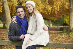 Romantic Couple Sitting On Fence In Autumn Woodland Royalty Free Stock Image