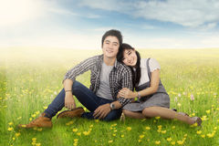 Romantic couple sitting at field in springtime Stock Images
