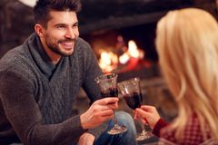 Romantic couple sitting on floor at burning fireplace and drink Royalty Free Stock Photography