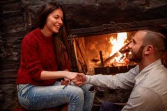 Romantic couple sitting on the floor in front of fireplace royalty free stock photography