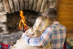 Romantic couple sitting in front of lit fireplace Royalty Free Stock Photo