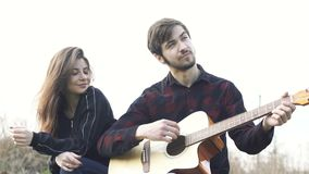 Romantic couple sitting and man playing the guitar for girlfriend. Outdoor. stock footage