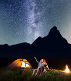 Romantic couple is sitting near the glowing tent and campfire and looking to the stars in the night sky Stock Photography