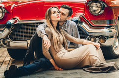 A romantic couple is sitting near red car. A man is hugging a woman. American classics. The guy and the girl next to the red car. Stock Photo