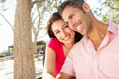 Romantic Couple Sitting On Park Bench Together Stock Photography