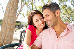 Romantic Couple Sitting On Park Bench Together Stock Photo