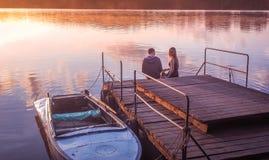 Romantic couple sitting pier golden sunset. Beautiful nature lake. man woman meet sunset. Beautiful couple outdoors near water Royalty Free Stock Photos