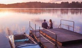 Romantic couple sitting pier golden sunset. Beautiful nature lake. man woman meet sunset. Beautiful couple outdoors near water Stock Images