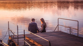 Romantic couple sitting pier golden sunset stroking dog. Beautiful nature lake. man woman meet sunset. Beautiful couple outdoors n Royalty Free Stock Images