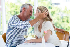 Romantic couple sitting at restaurant. Romantic couple with white wine while sitting at restaurant Royalty Free Stock Image
