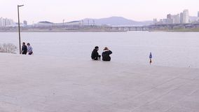 Romantic couple sitting on riverside, Seoul, South Korea