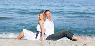 Romantic couple sitting on the sand Stock Photography