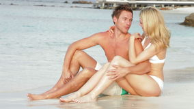 Romantic Couple Sitting By Shore At Beach stock video