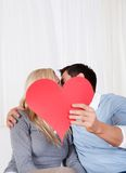 Romantic couple holding a red heart Stock Photos