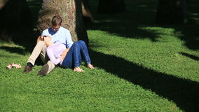Romantic couple sitting under a palm tree. A girl on the lap of a guy. A loving couple resting in a park on the grass. Under a tree stock video