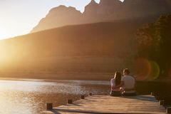 Romantic Couple Sitting On Wooden Jetty By Lake stock photography