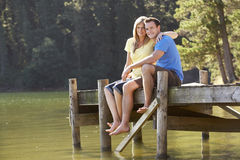 Romantic Couple Sitting On Wooden Jetty Looking Out Over Lake Stock Photo