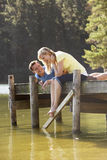 Romantic Couple Sitting On Wooden Jetty Looking Out Over Lake Royalty Free Stock Image
