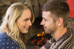 Romantic couple smiling in front of fireplace Stock Photography