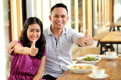 Romantic couple smiling and giving thumbs up Stock Photo