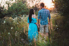 Romantic couple standing back in the sunset light in the park, holding hands Stock Photo
