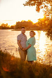 Romantic couple standing and kissing on background summer lake  sunset Stock Photography