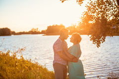Romantic couple standing and kissing on background summer lake  sunset Royalty Free Stock Photo