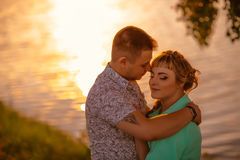 Romantic couple standing and kissing on background summer lake  sunset Stock Image