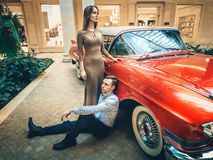 A romantic couple is standing by the red car. American classics. The guy and the girl near red car. Californian dream concept Royalty Free Stock Image
