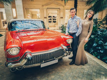 A romantic couple is standing by the red car. A man is hugging a woman. American classics. The guy and the girl next to the red ca Royalty Free Stock Photo