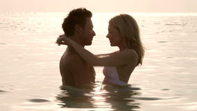 Romantic Couple Standing In Sea At Sunset stock video