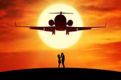 Romantic couple standing under flying aircraft Royalty Free Stock Photo