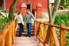 Romantic couple standing on wooden bridge. Romentic couple standing on wooden bridge in autumn park and looking at each other stock images