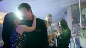 Romantic couple stands close together on background of bright lights in club stock footage